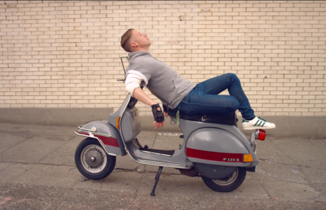 Macklemore reclines on his moped in Downtown